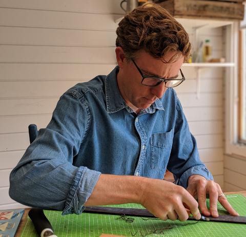 Matt at Coast Leather bevelling the edges of a belt.